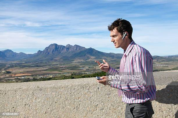 young man with mobile phone and hands-free device, (afrikaanse taal monument, paar, south africa) - taal foto e immagini stock