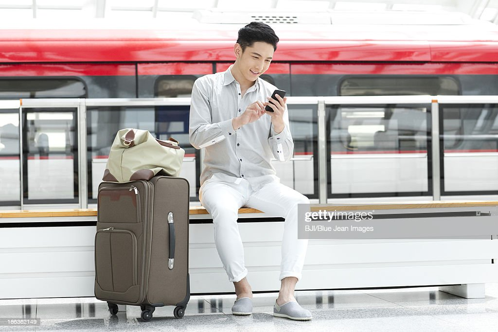 Young man with mobile phone at subway station : Stock-Foto