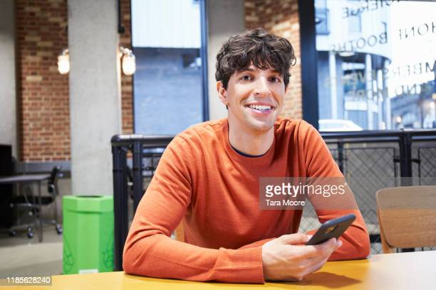 young man with mobile phone in office - happiness stock pictures, royalty-free photos & images