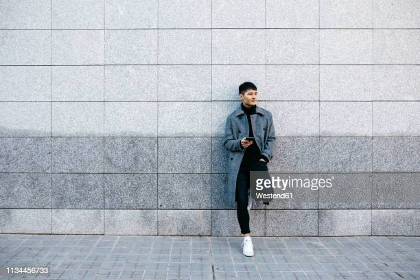 young man with mobile phone leaning against wall waiting - 待つ ストックフォトと画像