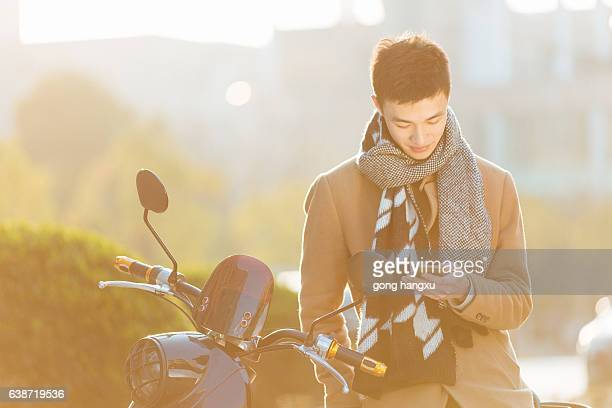 young man with mobile phone on motorcycle in modern city