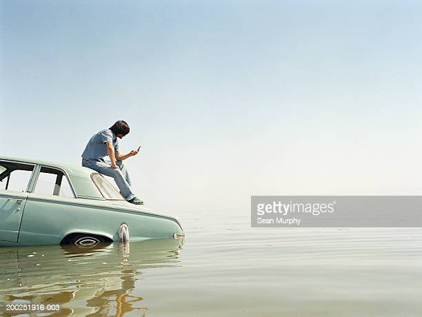 Young man with mobile phone sitting on roof of car in water