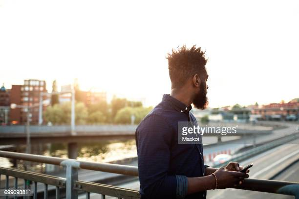 Young man with mobile phone standing on bridge against sky