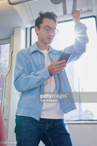 young man with mobile phone standing on commuter train - 通勤電車 ストックフォトと画像