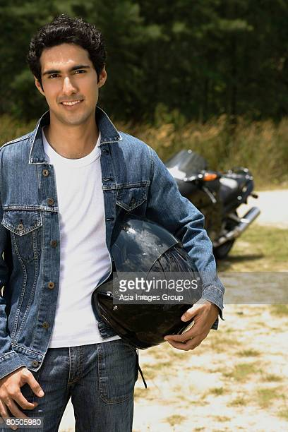 young man with motorcycle helmet smiling at camera - capacete capacete esportivo - fotografias e filmes do acervo