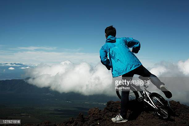 young man with mountain bike in the mountains