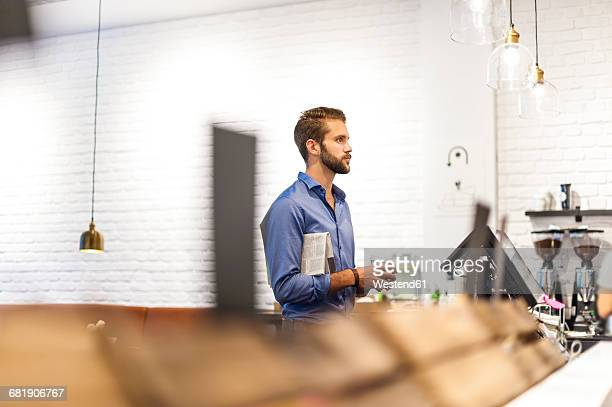 Young man with newspaper and coffee to go at counter of a coffee shop