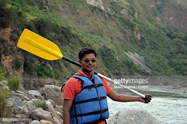 Young Man With Oar Standing By River