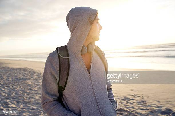Young man with on beach at sunrise looking on the ocean