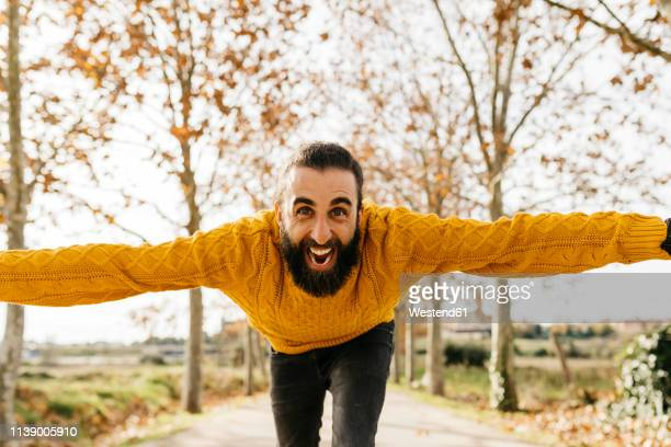 young man with open arms and happy in a park in autumn - temptation stock pictures, royalty-free photos & images