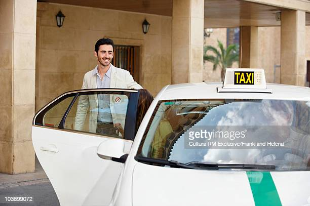 Young man with open taxi door