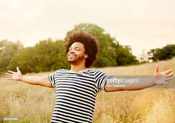 young man with outstretched hands in field. - freedom stock pictures, royalty-free photos & images