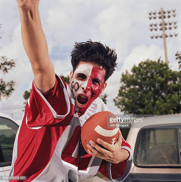 young man with painted face, cheering and holding football - football body paint stock photos and pictures