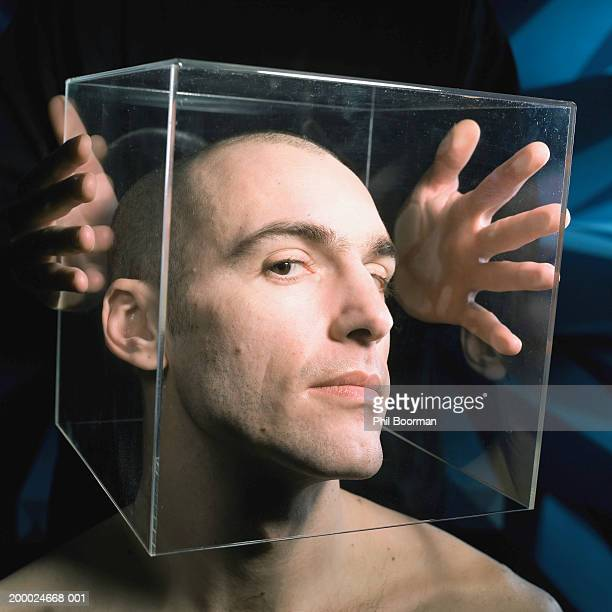 Young man with perspex cube over head, portrait