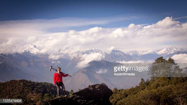 young man with photographic equipment relaxes on mountain ridge - simple living stock pictures, royalty-free photos & images