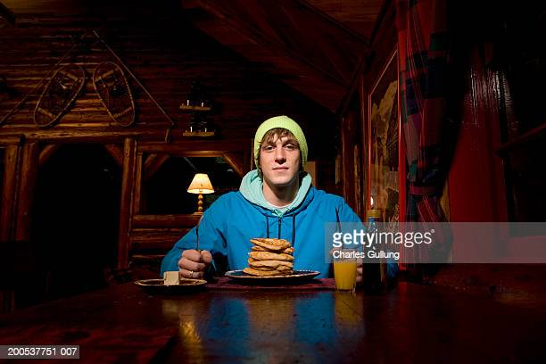 Young man with plate of pancakes sitting at dining table in log cabin
