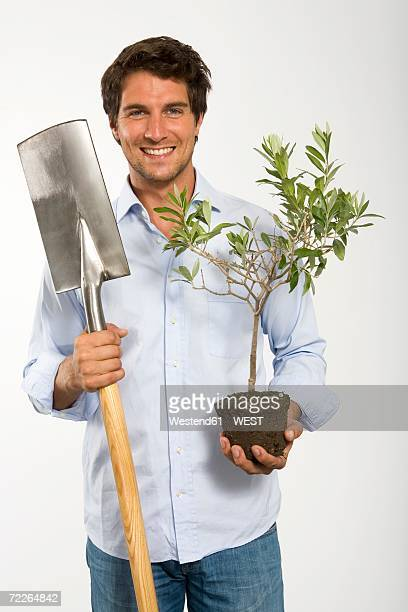 Young man with pot plant and spade, smiling, close-up, portrait