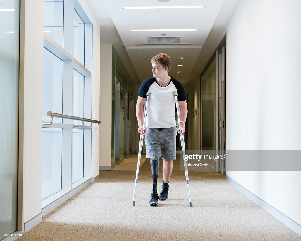 Young man with prosthetic leg on crutches : Stock Photo
