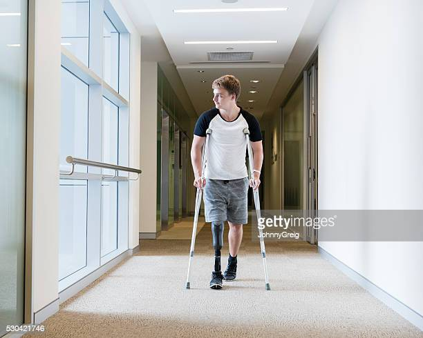 young man with prosthetic leg on crutches - crutch stock photos and pictures