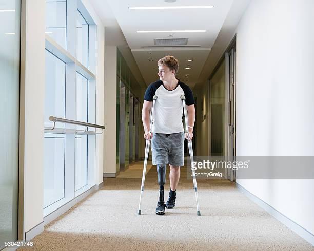 Junger Mann mit einer Beinprothese auf Krücken