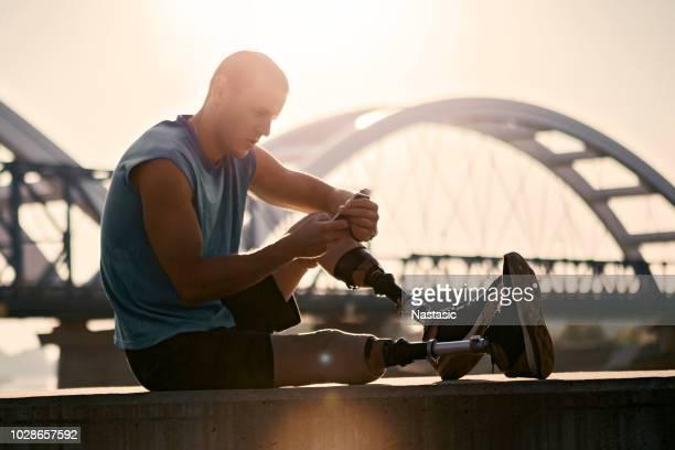 Jonge man met prothetische been zitten buiten nemen pauze
