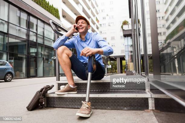 young man with prosthetic leg sitting in front of the office building while talking on a smart phone - artificial limb stock photos and pictures