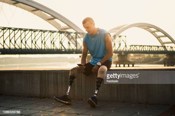young man with prosthetic leg sitting outside texting - paraplegic stock photos and pictures