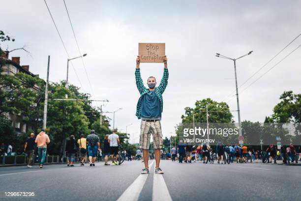 young man with protective face mask, surrounded by a crowd, holding a poster in his hands. young activist / protester against the corruption. human rights and social issues concept. - extremism stock pictures, royalty-free photos & images