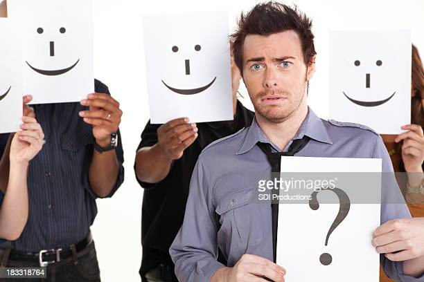 Young Man With Question Mark Sign Among Happy People
