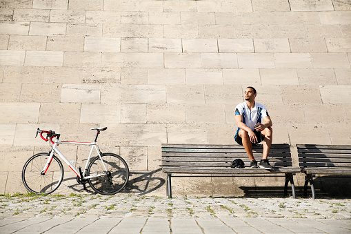 Young man with racing bicycle having a break - gettyimageskorea
