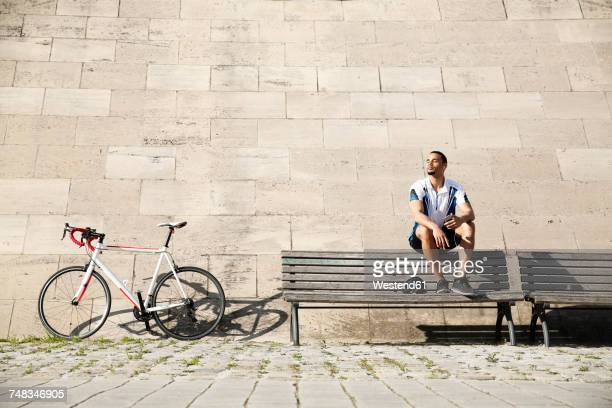 Young man with racing bicycle having a break