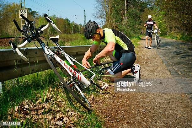 Jeune homme avec course de vélo de route de réparation de crevaison