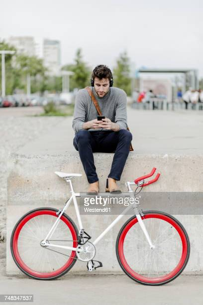 Young man with racing cycle sitting on a wall listening music with headphones
