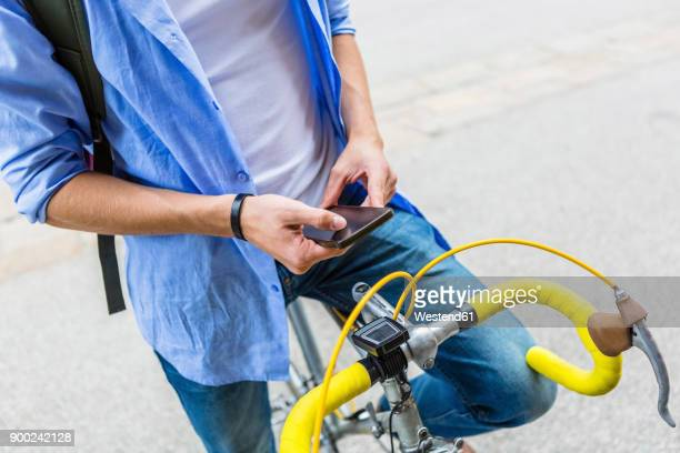 Young man with racing cycle using cell phone, partial view
