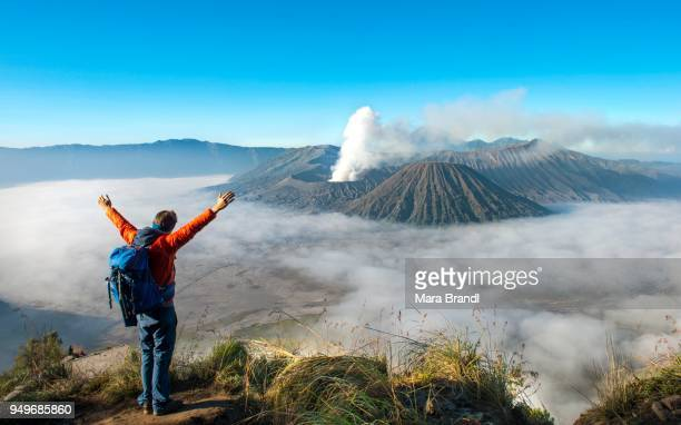young man with raised arms in front of volcanic landscape, view in tengger caldera, smoking volcano gunung bromo, in front mt. batok, in the back mt. kursi, mt. gunung semeru, national park bromo-tengger-semeru, java, indonesia - mount bromo stock pictures, royalty-free photos & images
