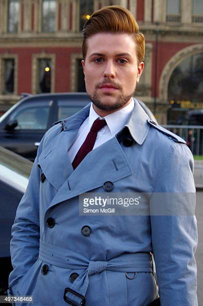 Young man with red hair and neatly trimmed beard wearing a shirt tie and blue trench coat near Albert Hall London UK