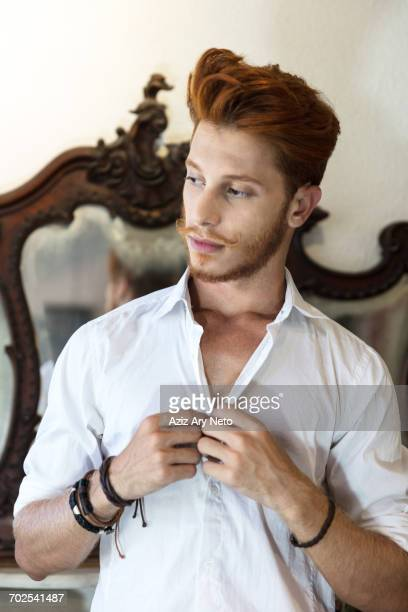 young man with red hair, buttoning shirt - ポンパドール ストックフォトと画像