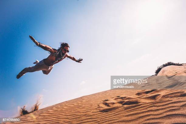 young man with retro glasses doing parkour jump in desert - steampunk stock photos and pictures