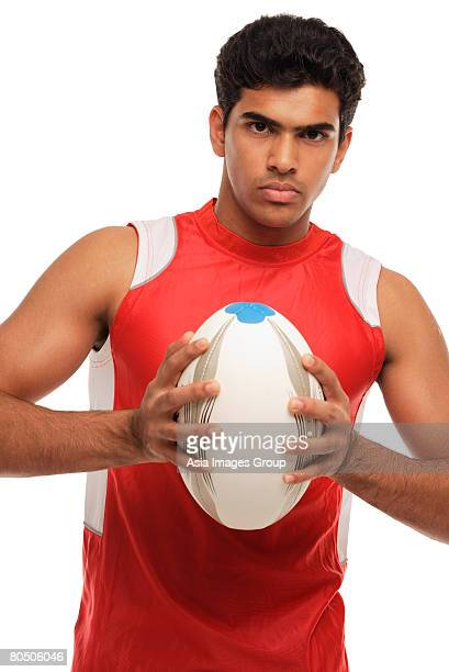 Young man with rugby looking at camera