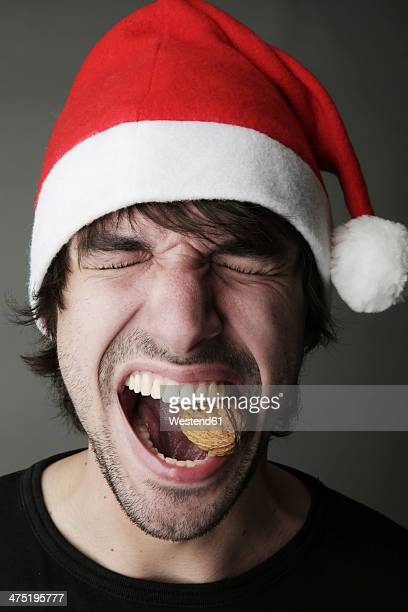 Young man with Santa hat trying to crack a walnut with his teeth, studio shot