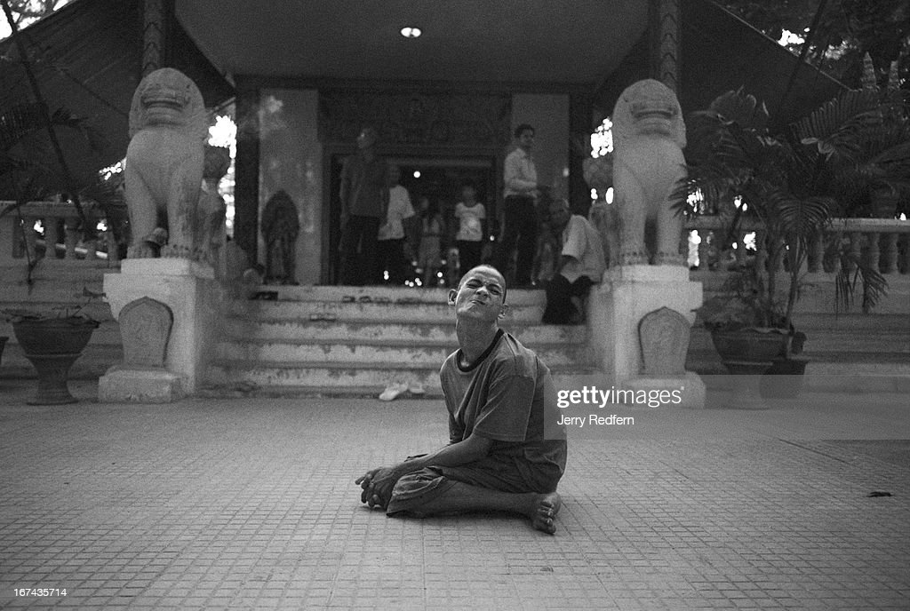 A young man with severe birth defects poses for a photo in front of a small Buddhist temple in Siem Reap. He didn't beg for money, but asked that passers-by would take his photo..