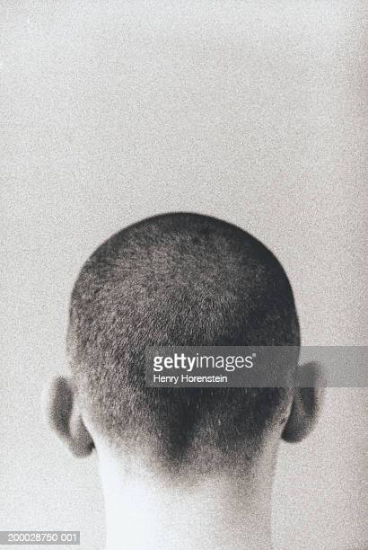 Young man with shaved head, high section, rear view (grainy, B&W)