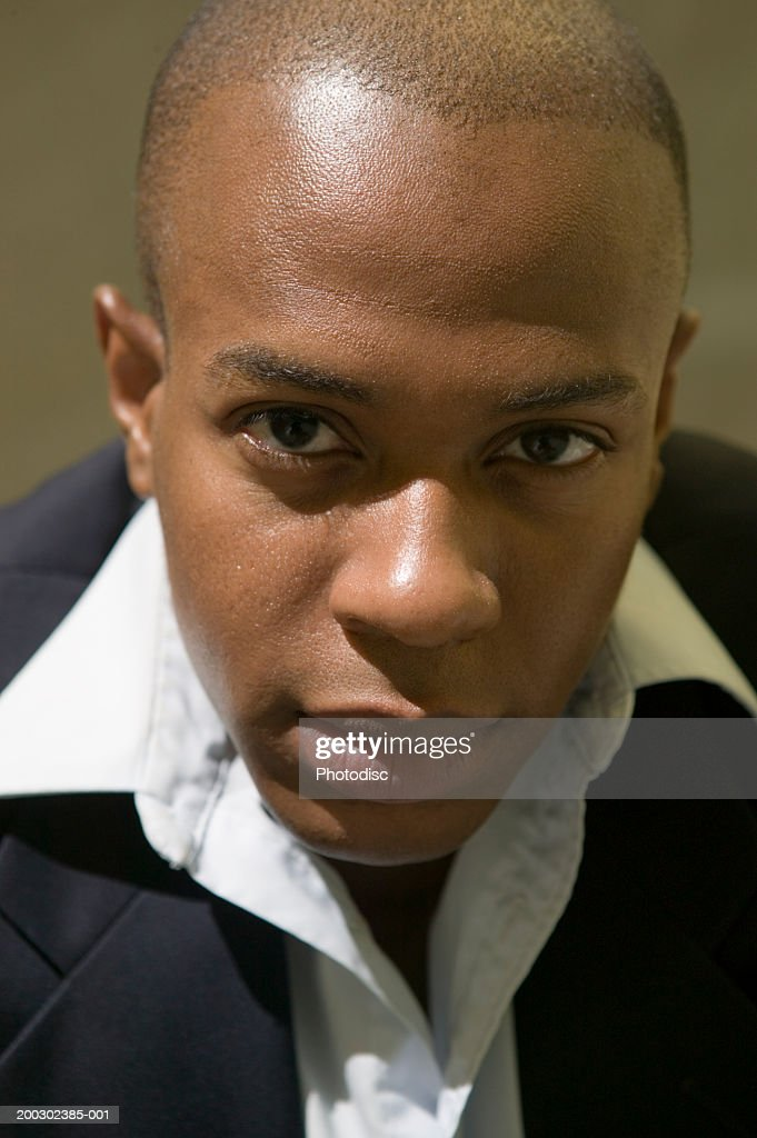 Young Man With Shaved Head Sitting Indoors Portrait