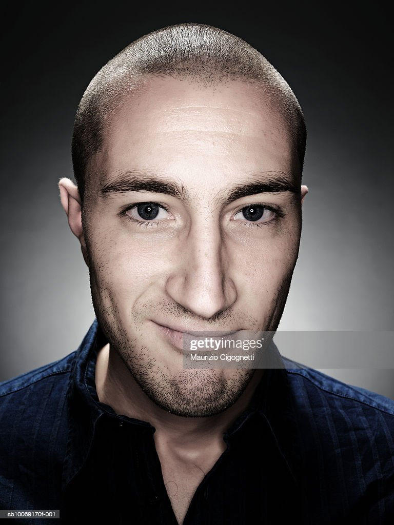 Young man with shaved head, smiling, portrait, studio shot : Stockfoto