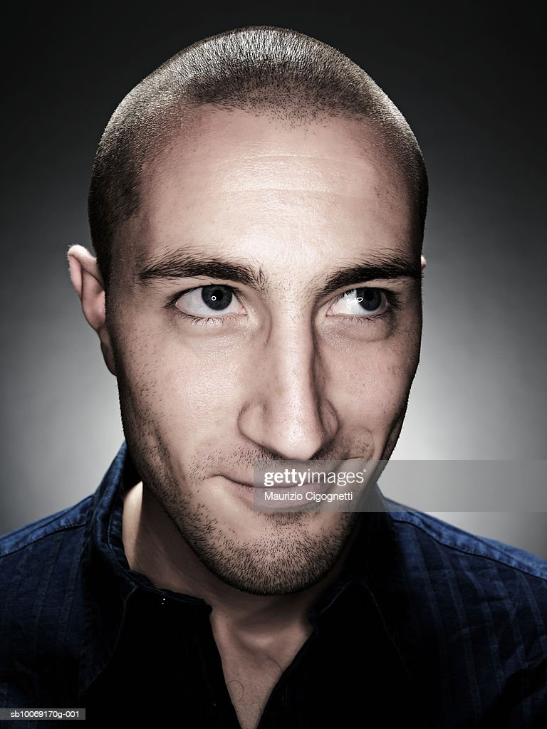 Young man with shaved head, smiling, studio shot : Stockfoto