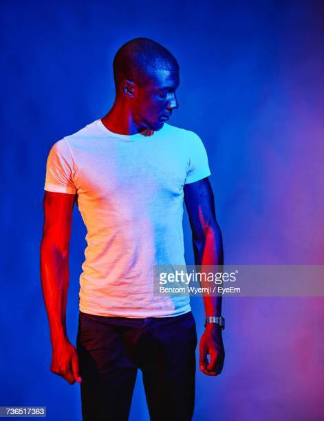 young man with shaved head standing against colored background - light effect stock pictures, royalty-free photos & images