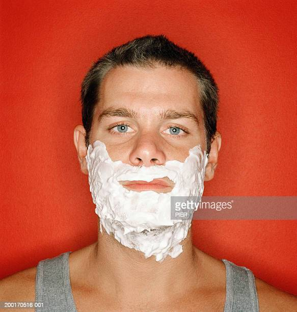 Young man with shaving foam on face, portrait, close-up
