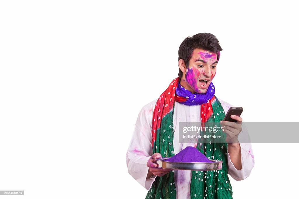 Young man with shocked expression after reading sms : Stock Photo