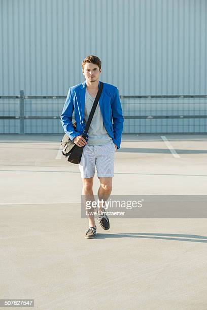 Young man with shoulder bag strolling across empty parking lot