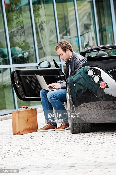 Young man with sitting in his sports car using laptop
